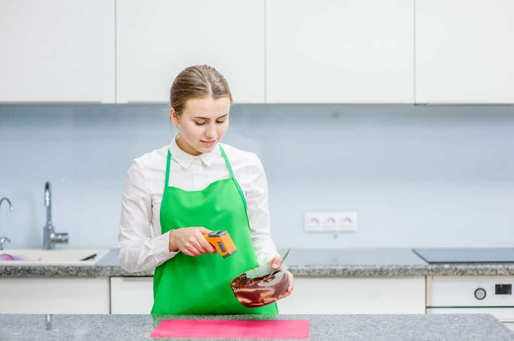 Na foto uma mulher dentro de uma cozinha apontando um termômetro para uma tigela.