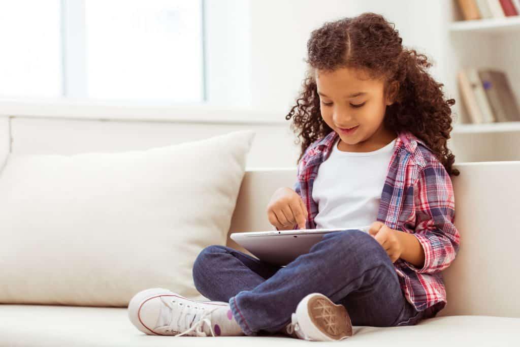 Na foto uma menina sentada em um sofá com um tablet nas mãos.
