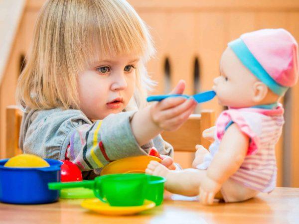 Menina sentada em uma cadeira de frente para uma boneca que está na mesa, colocando uma colher de plástico na boca da boneca.
