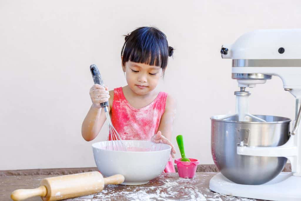 Foto de uma menina toda suja de farinha, mexendo uma massa rosa em uma tigela, em uma bancada com uma batedeira Kitchen Aid, um rolo para massas e um pequeno potinho com colher.