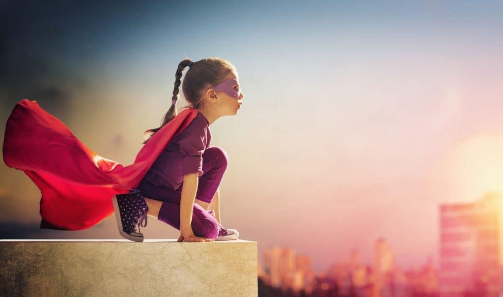 Na foto uma menina em cima de um prédio fantasiada de heroina.