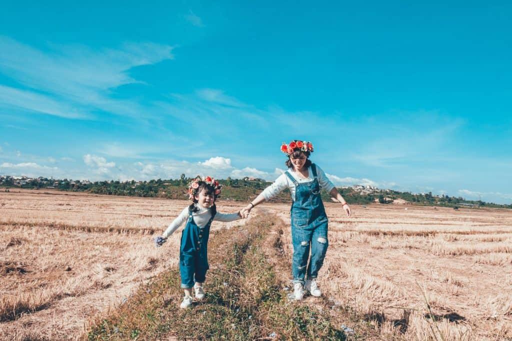 Na foto uma menina e uma mulher de mãos dadas em um campo usando macacões jeans e flores na cabeça.