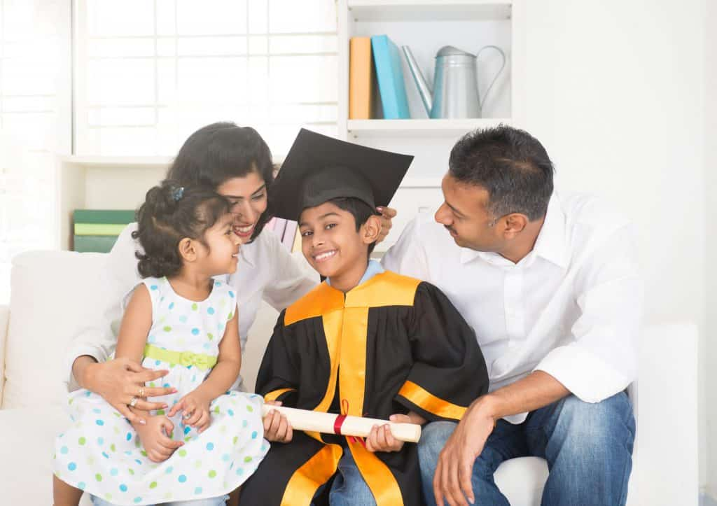 Na foto uma família sentada em um sofá com um menino vestindo beca no meio.