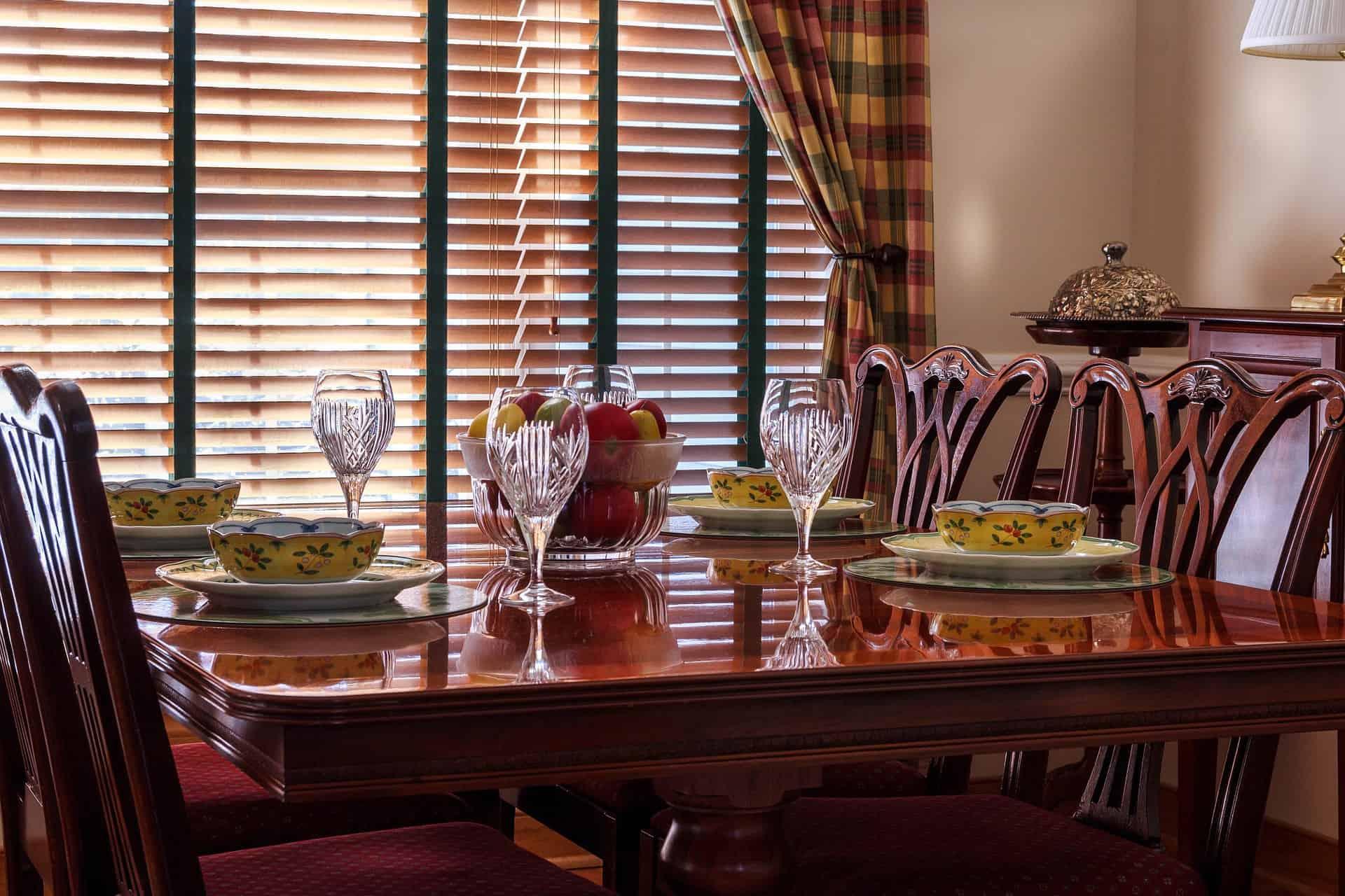 Imagem de mesa de jantar com taças e fruteira.