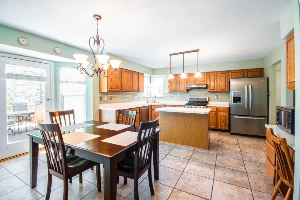 Imagem de uma mesa com quatro cadeiras no centro de uma cozinha.