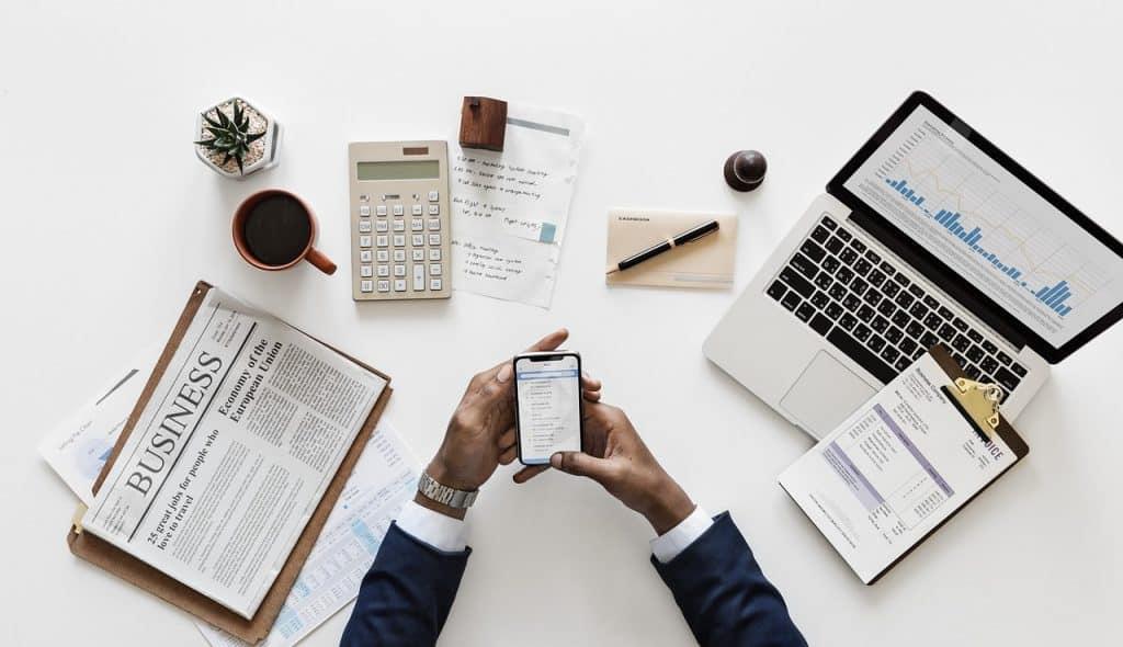 Na foto um mesa com uma pessoa usando um celular e alguns papéis, notebooks, xícara e calculadores em cima dela.
