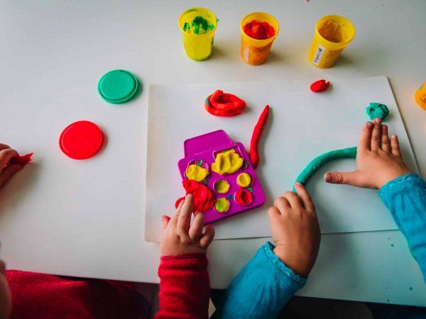 Mãos de duas crianças brincando com massinha de modelar.