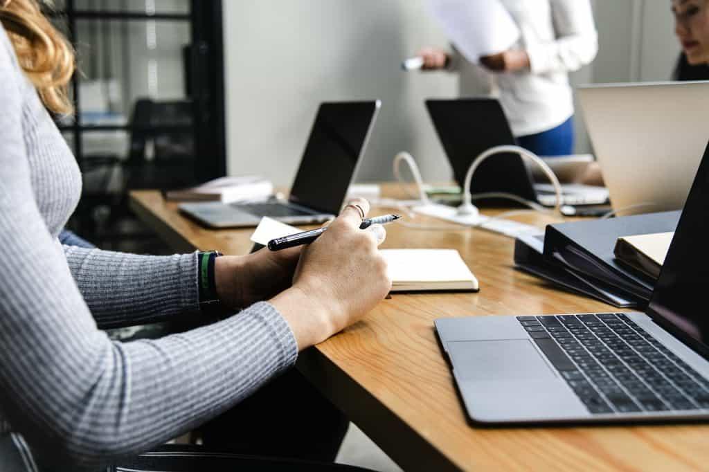Mesa com pessoas usando notebook, e extensão elétrica.