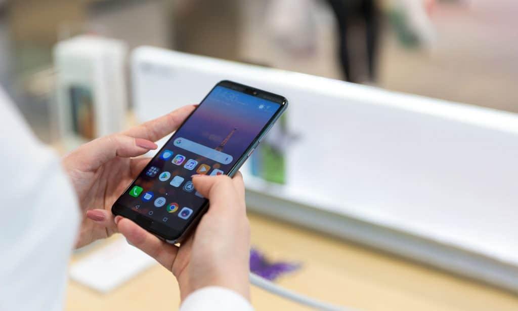 Na foto as mãos de uma mulher segurando um celular Huawei.