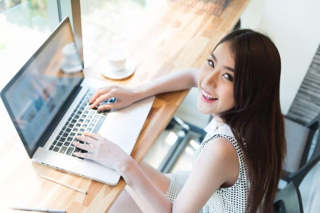 Na foto uma mulher sentada em uma cafeteria usando um notebook.