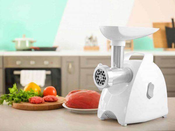 Na foto um moedor de carnes elétrico em cima de uma bancada em uma cozinha com pratos de carnes ao fundo.