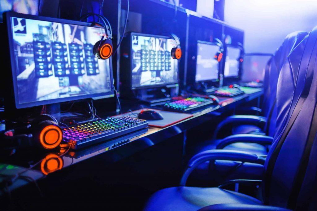 Em uma Lan House existe uma mesa com 4 monitores, com cadeiras na frente de cada monitor.