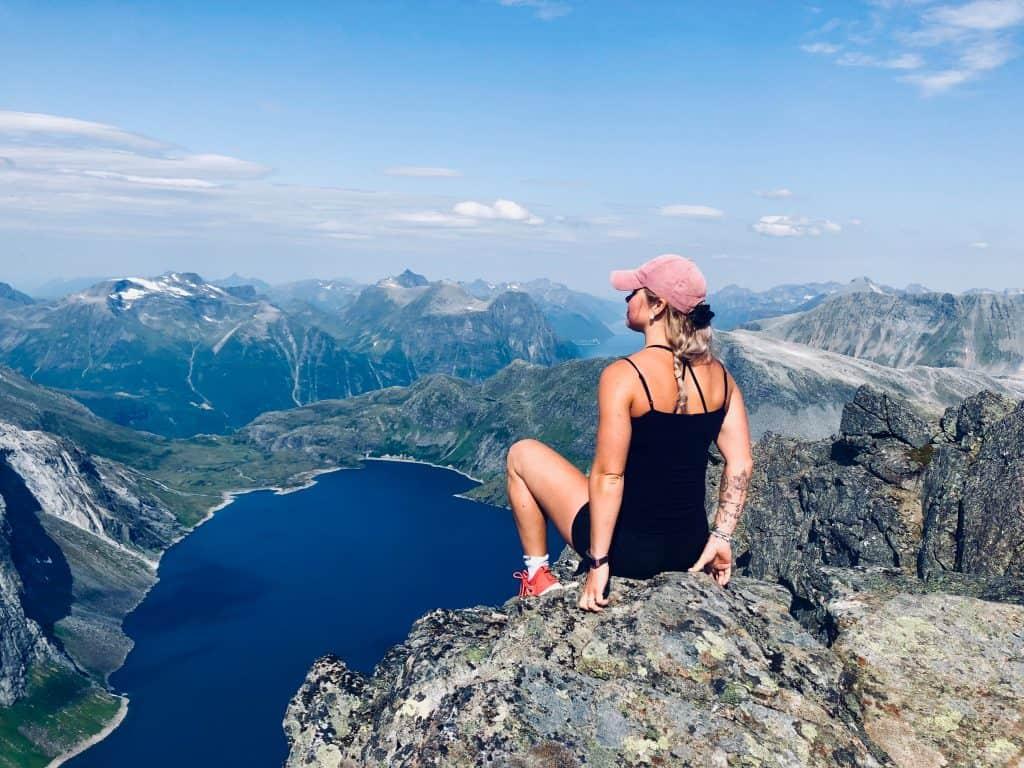 Na foto uma mulher em cima de uma pedra olhando para uma paisagem.
