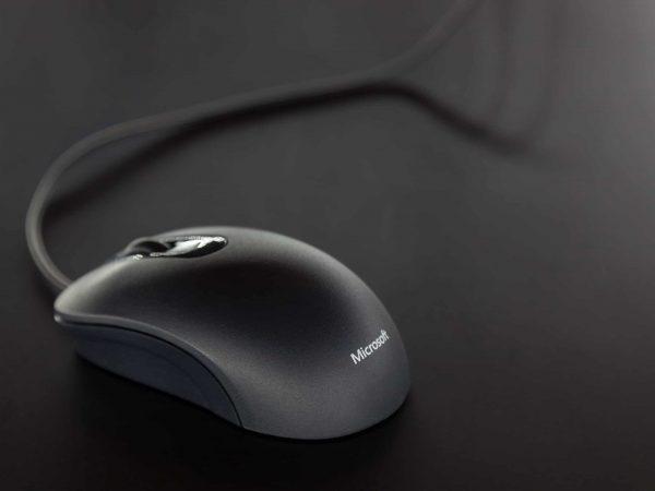 Na foto um mouse com fio preto da Microsoft.
