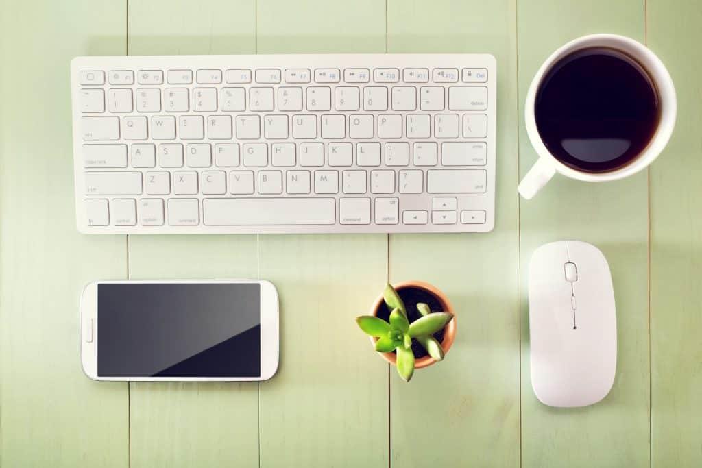 Imagem de mouse sobre mesa com teclado, celular, xícara de café e planta em volta.