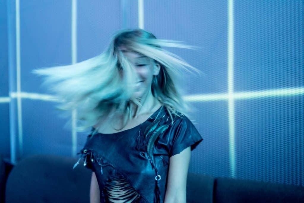 Foto de uma mulher loira e sorridente, em movimento, dançando e jogando os cabelos. Ela veste roupa com recortes.