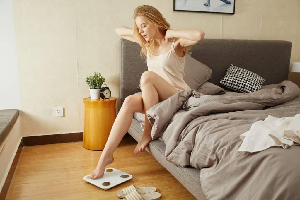 Imagem de uma mulher apoiando um dos pés em uma balança.