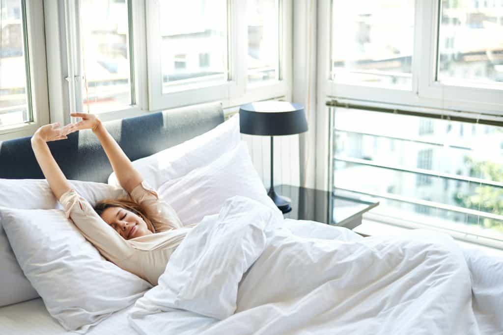 Na foto uma mulher se espreguiçando em uma cama dentro de um quarto repleto de janelas de vidro.