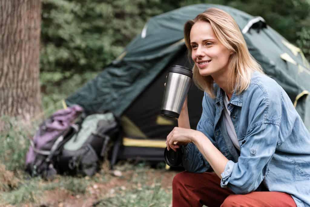 Imagem de uma mulher tomando café em um copo térmico durante um acampamento.