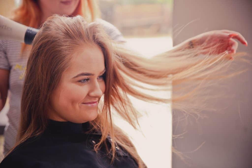 Imagem de uma cabelereira secando o cabelo de uma cliente.