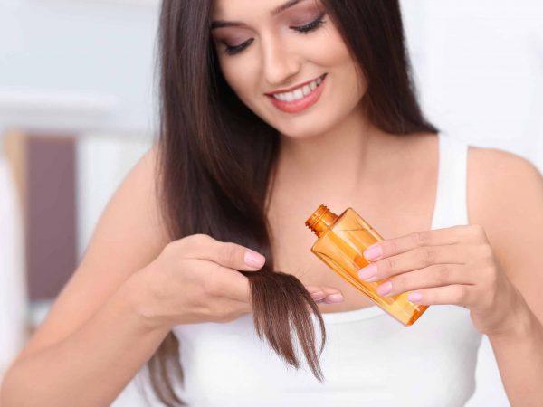 Imagem de uma mulher aplicando óleo de argan no cabelo.