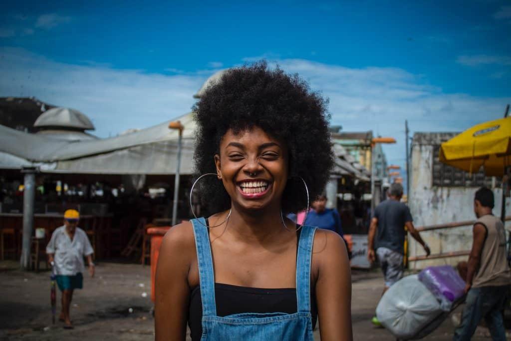 Moça sorri para foto usando brincos de argola grandes.