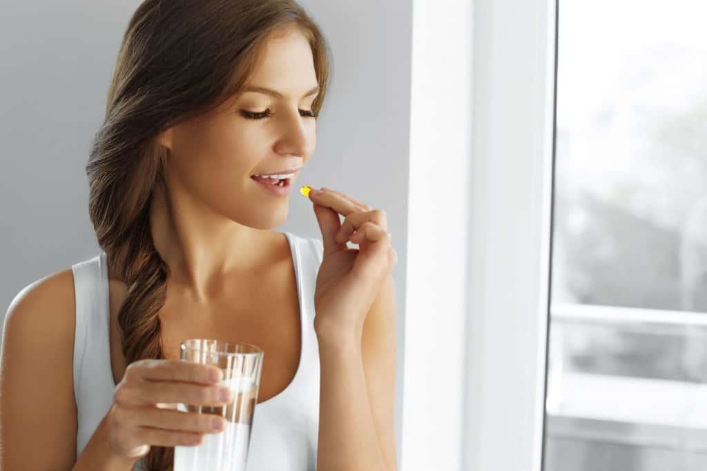 Mulher tomando vitamina.