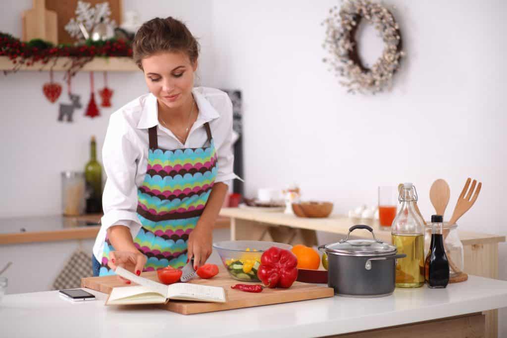 Moça prepara ingredientes de receita enquanto consulta livro de gastronomia.