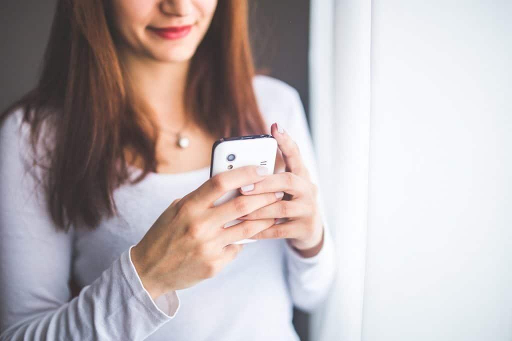 Mulher digitando no celular.
