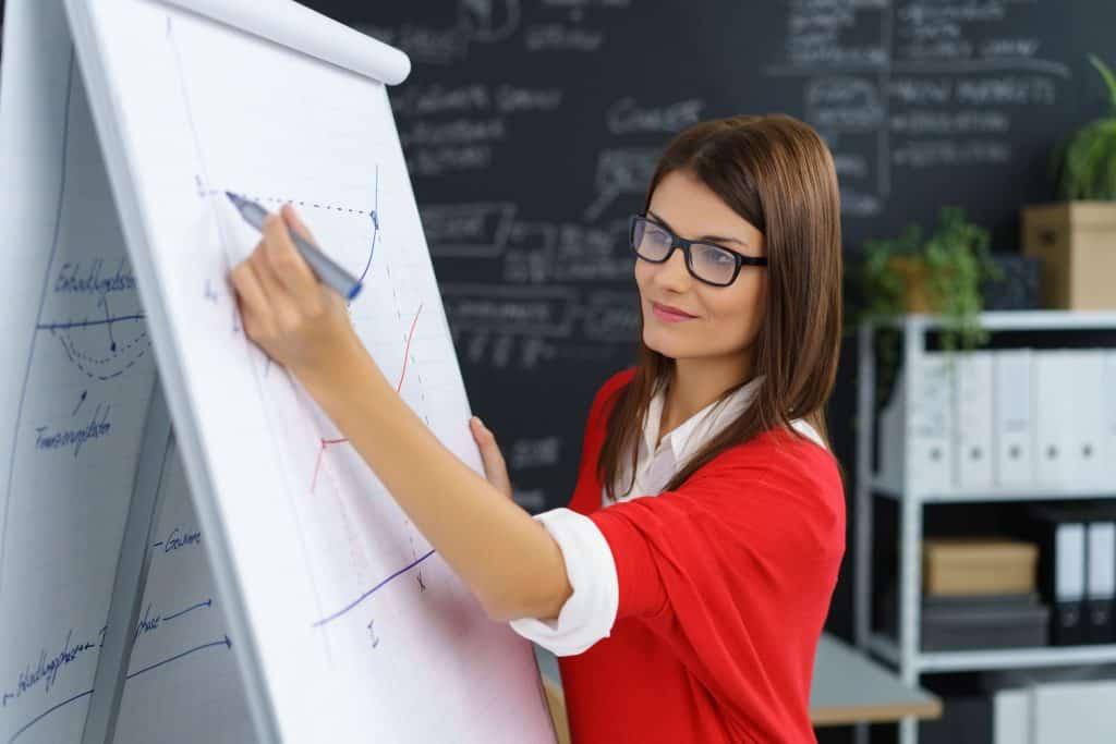 Na foto uma mulher escrevendo em um flip chart de papel.