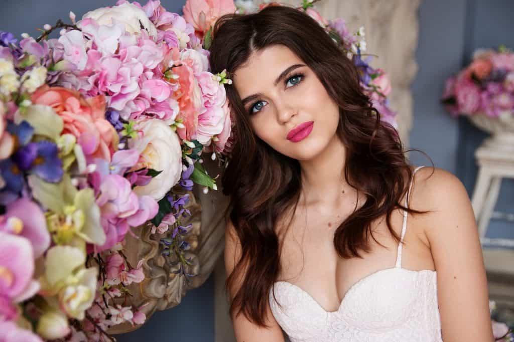 Imagem de uma mulher ao lado de um arranjo de flores.