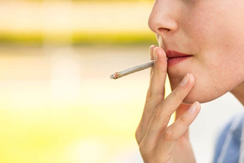 Imagem mostra uma mulher fumando um cigarro artesanal.