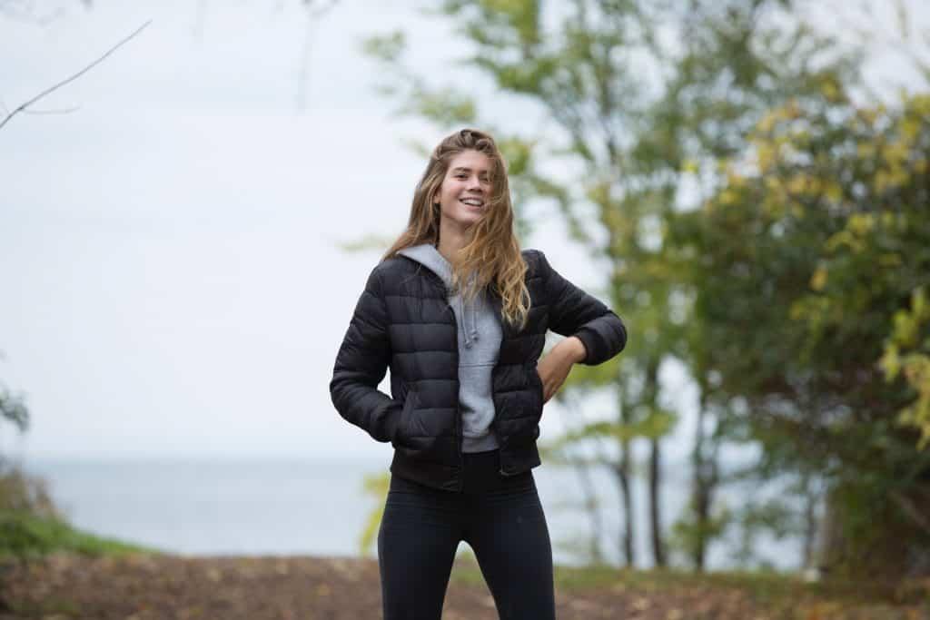 Imagem de uma mulher vestida com uma jaqueta Adidas.