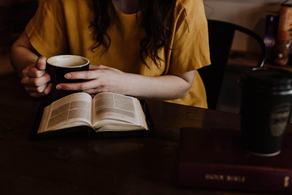 Uma pessoa está sentada à mesa segurando uma xícara enquanto lê um livro, aberto em cima da mesa.