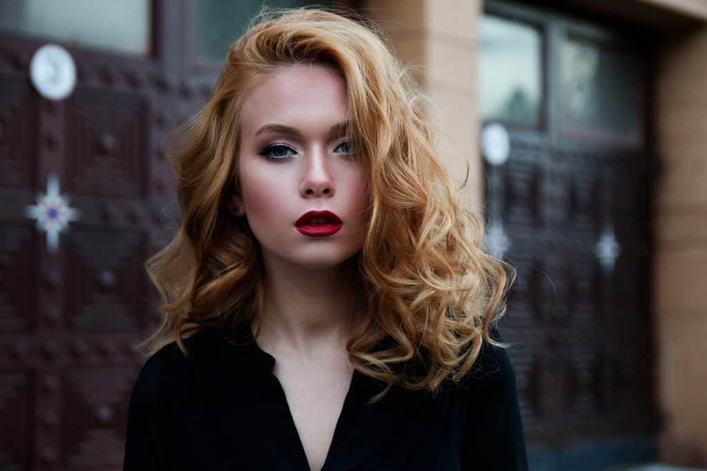 Mulher loira maquiada com cabelo ondulado.