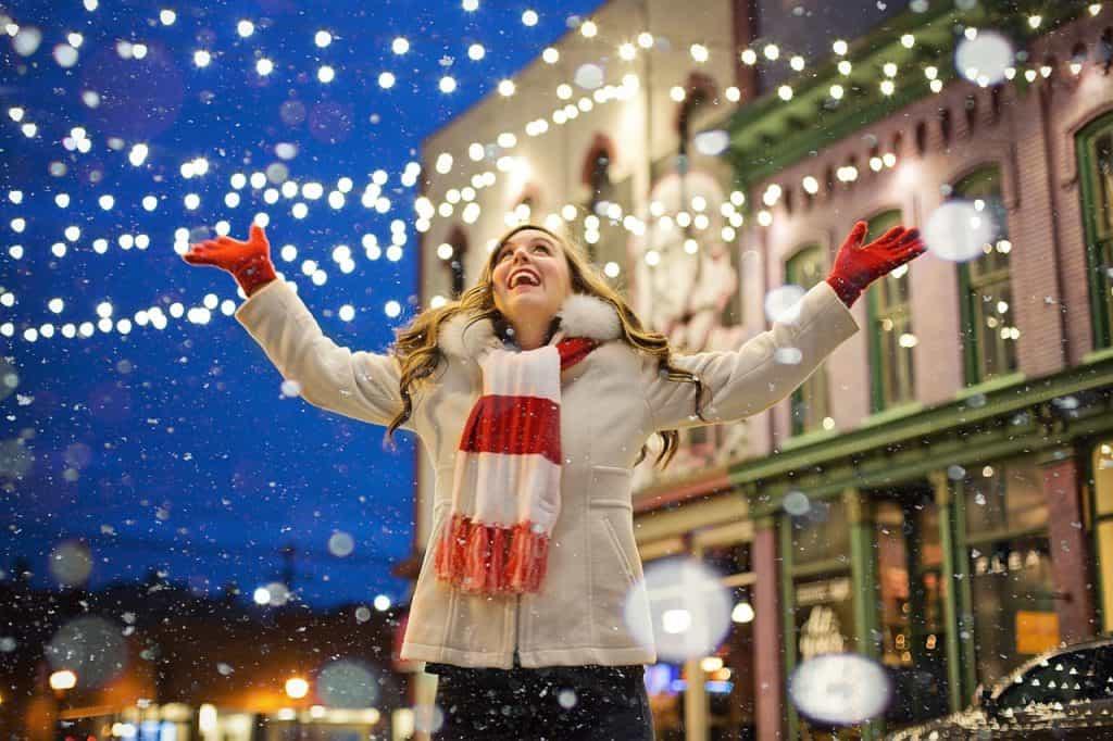 Imagem de uma mulher em uma rua com decoração natalina.
