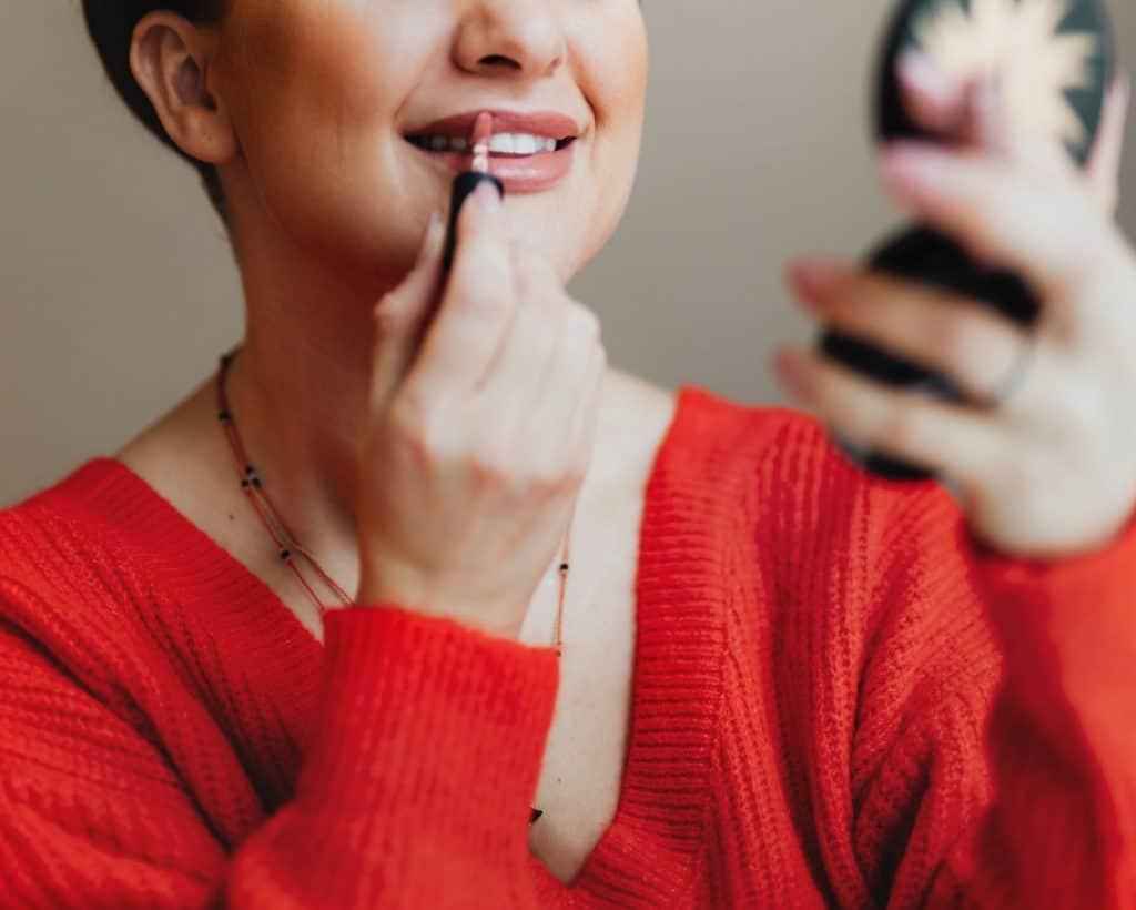 Mulher passando gloss com a ajuda de um pequeno espelho.