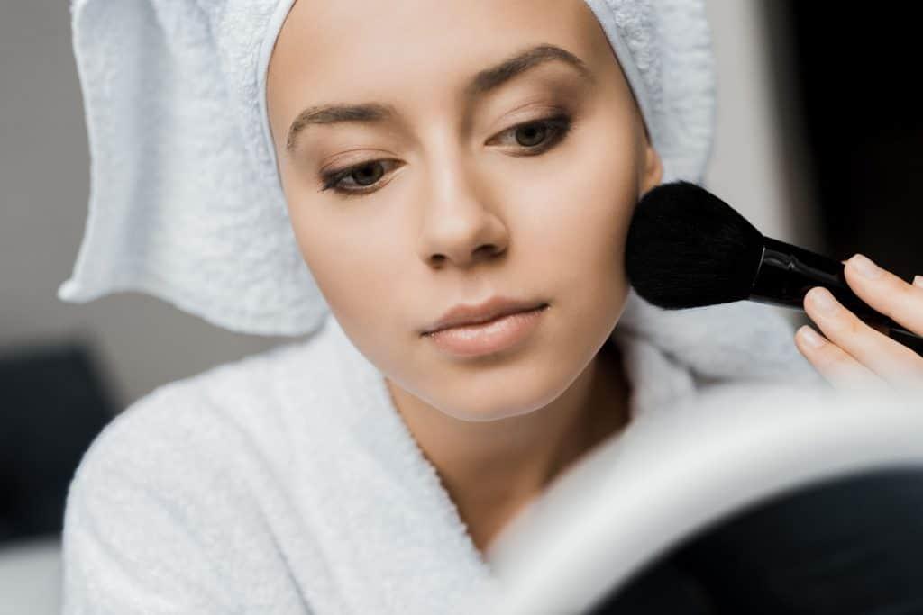Mulher utilizando um pincel de maquiagem.