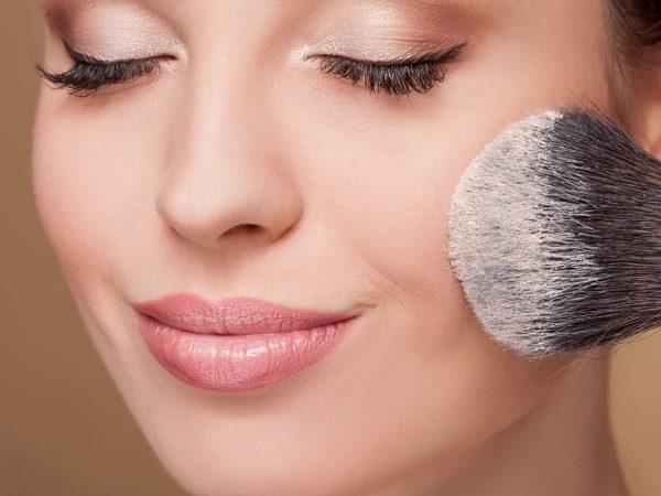 Close up do rosto de uma mulher sorrindo com os olhos fechado e passando o pincel de pó translúcido na bochecha.