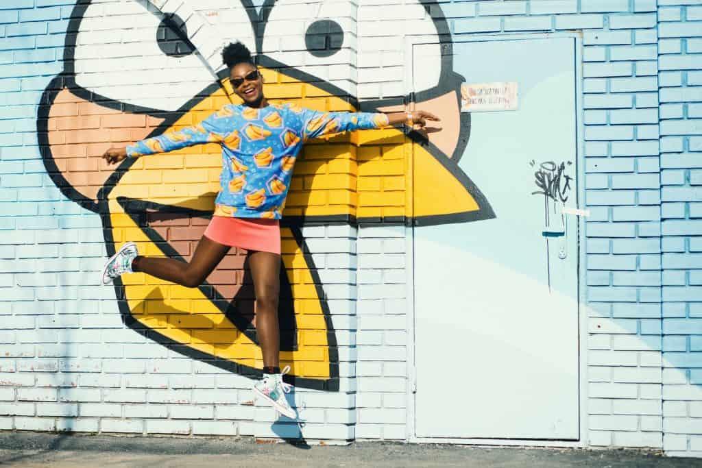 Na foto uma mulher pulando saltando em frente a uma parede azul de tijolinhos.