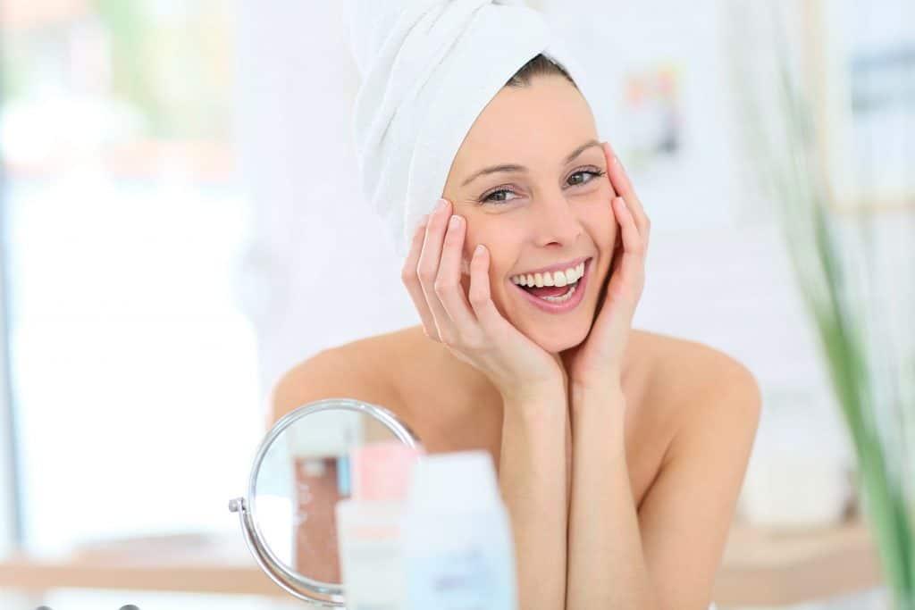 Moça com as mãos no rosto com cabelos molhados enrolados em toalha de banho.