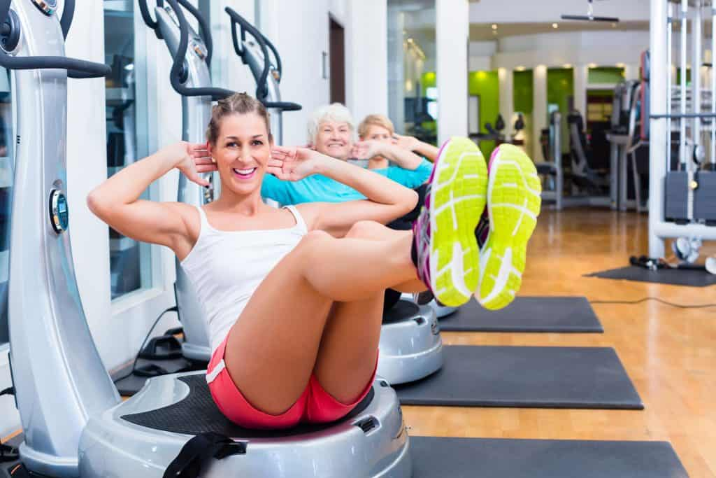 Na foto três mulheres fazendo exercícios em uma plataforma vibratória.