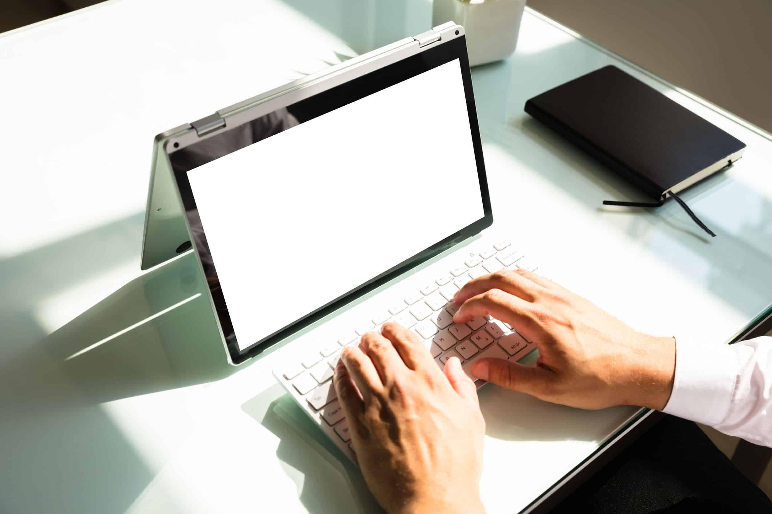 Na foto um homem usando um notebook 2 em 1 em cima de uma mesa.