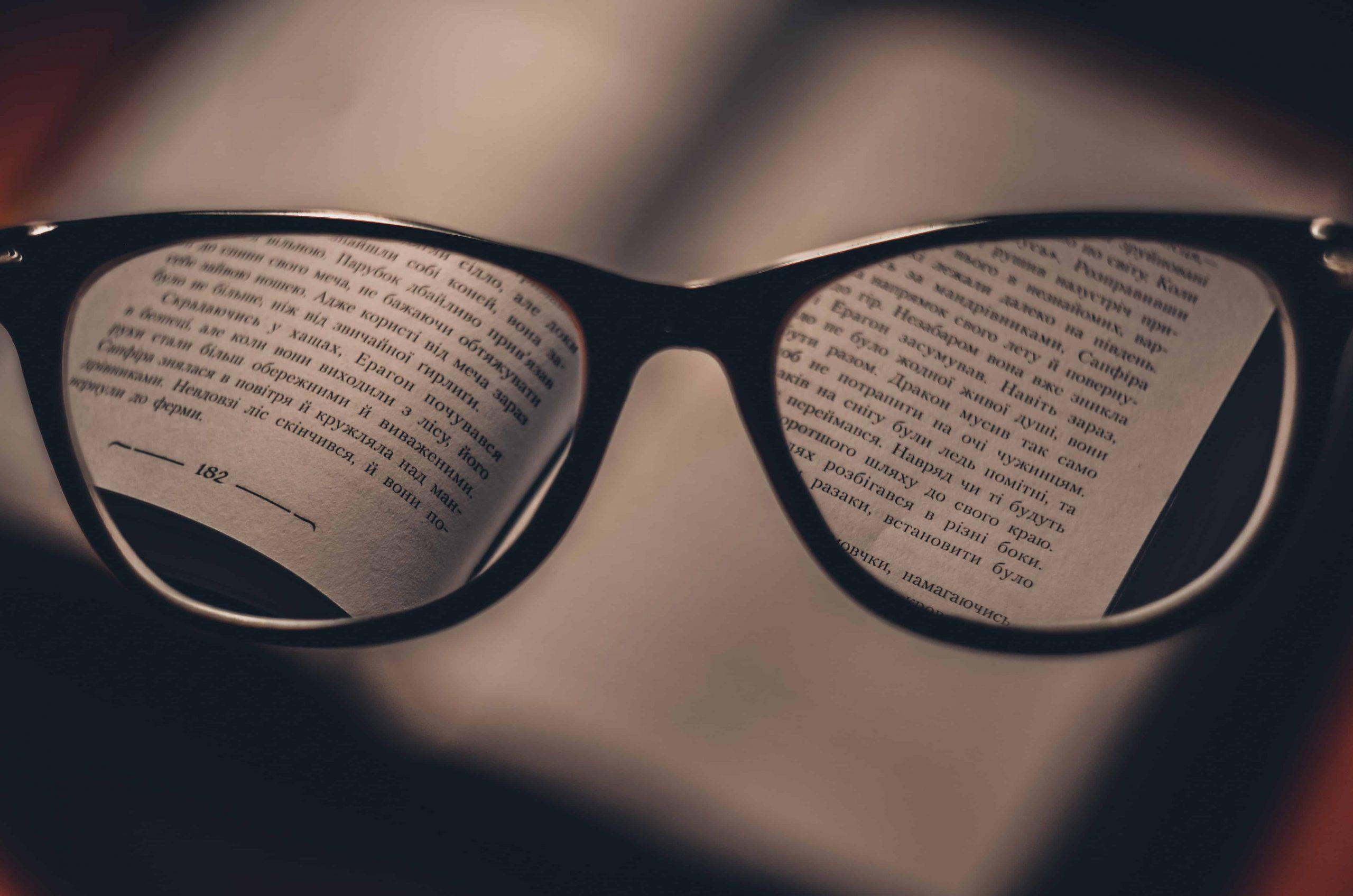 Um livro está aberto, porém desfocado. Só é possível lê-lo através das lentes do óculos, presente no centro da imagem.