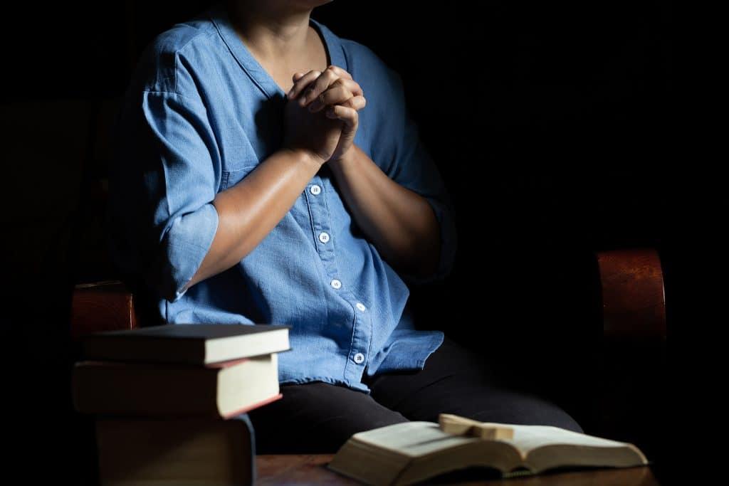 Imagem de uma mulher sentada com a palma de uma mão encostada na outra e apenas com o corpo abaixo do pescoço aparecendo, com vários livros a sua volta.
