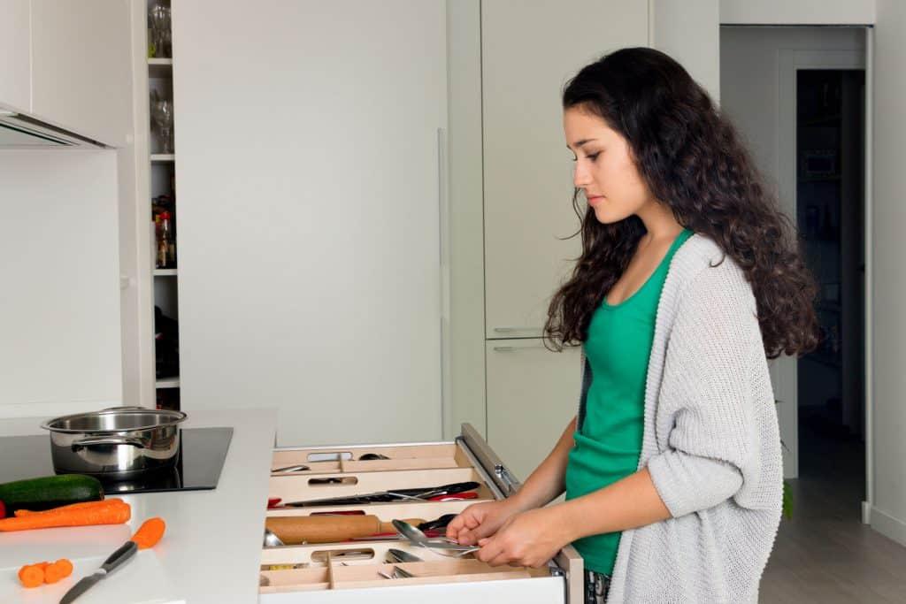Moça pega talheres em gaveta organizada com divisor.
