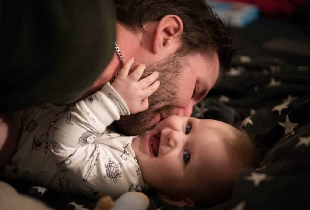 Na foto um homem dando um beijo na bochecha de uma bebê sorrindo.