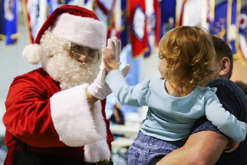 Papai Noel cumprimenta menina no colo do pai.