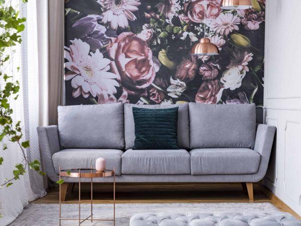 Papel de parede com estampa floral com sofá na frente.
