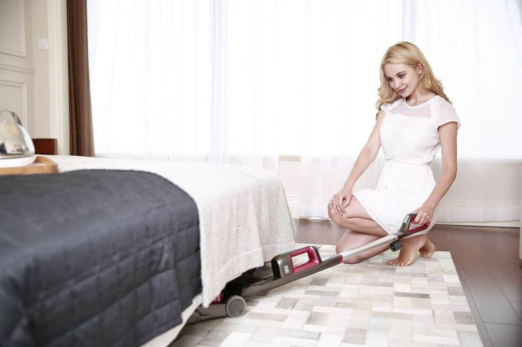 Imagem de uma mulher passando aspirador de pó embaixo da cama.